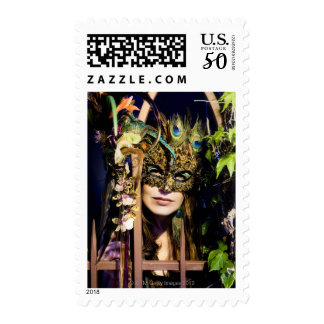 Woman wearing a mask looking out from and iron postage