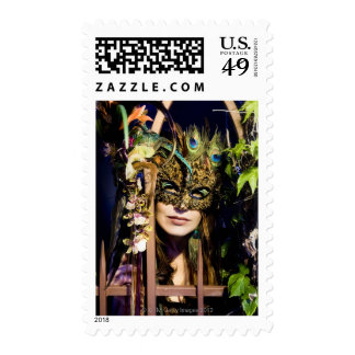 Woman wearing a mask looking out from and iron stamps