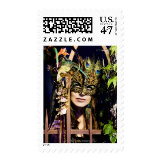 Woman wearing a mask looking out from and iron postage stamp