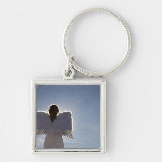 Woman wearing angel wings, rear view, three key chains