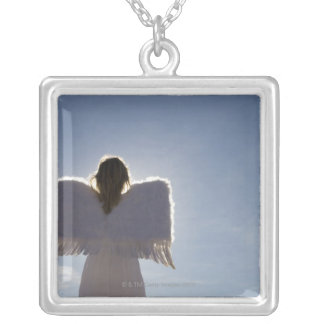 Woman wearing angel wings, rear view, three square pendant necklace
