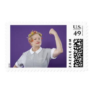 Woman wearing hair curlers, tensing arm muscles, postage
