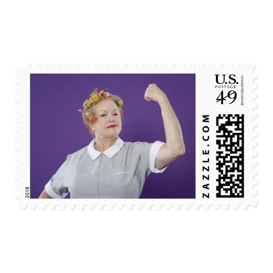 Woman wearing hair curlers, tensing arm muscles, postage