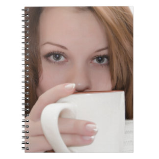 Woman with a cup. spiral notebook