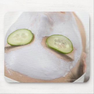 Woman with face mask and cucumber slices on mouse pad