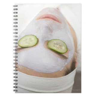 Woman with face mask and cucumber slices on notebook