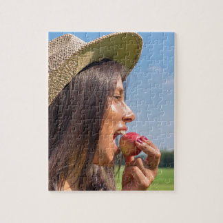 Woman with hat eating red apple outside jigsaw puzzle