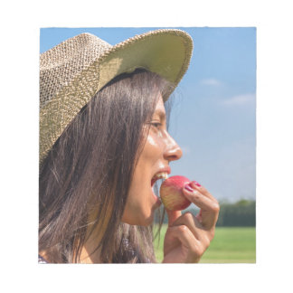 Woman with hat eating red apple outside notepad