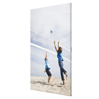 Woman with her grandson playing beach volleyball canvas print