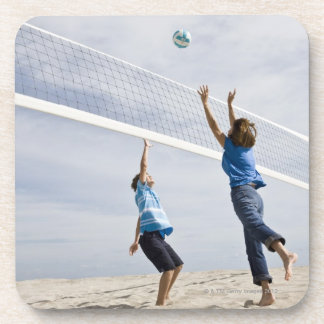 Woman with her grandson playing beach volleyball coaster