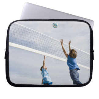 Woman with her grandson playing beach volleyball laptop sleeve