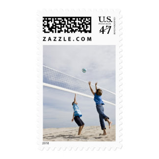 Woman with her grandson playing beach volleyball postage