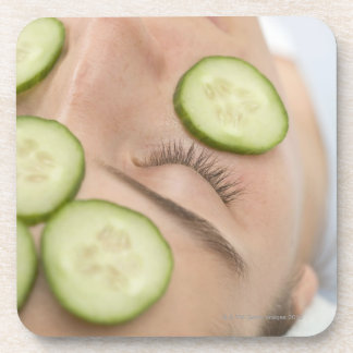 Woman with slices of fresh cucumber on her face, beverage coaster
