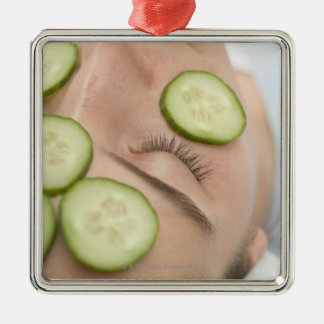 Woman with slices of fresh cucumber on her face, metal ornament