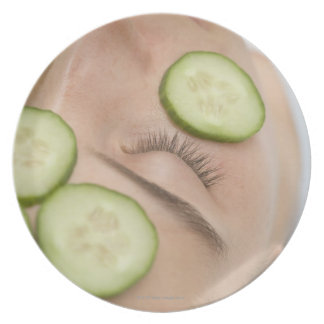 Woman with slices of fresh cucumber on her face, plates
