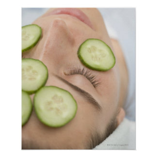 Woman with slices of fresh cucumber on her face, poster