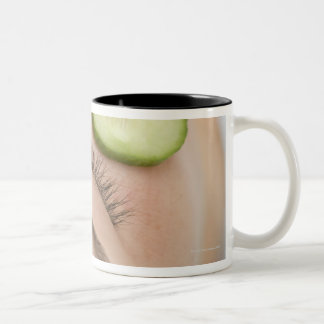 Woman with slices of fresh cucumber on her face, Two-Tone coffee mug