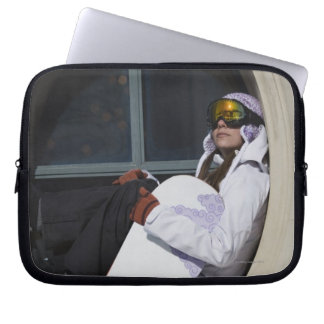 Woman with snowboard sitting in window laptop sleeve