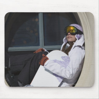 Woman with snowboard sitting in window mouse pad