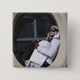 Woman with snowboard sitting in window pinback button