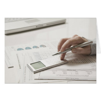 Woman working on financial paperwork and greeting card