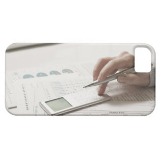 Woman working on financial paperwork and iPhone 5 covers