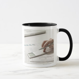 Woman working on financial paperwork and mug