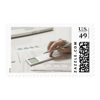 Woman working on financial paperwork and postage stamp