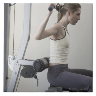 Woman working out with weights large square tile