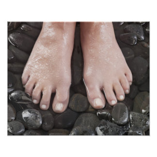Woman's feet on pebbles posters