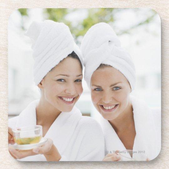 Women in bathrobes drinking tea at spa beverage coaster