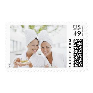 Women in bathrobes drinking tea at spa postage