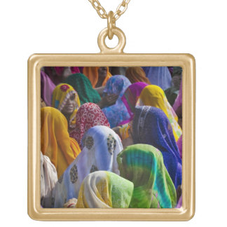 Women in colorful saris gather together gold plated necklace