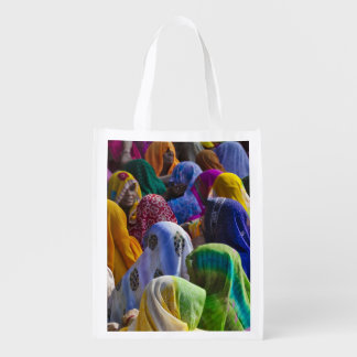Women in colorful saris gather together reusable grocery bag
