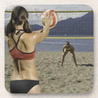 Women playing volleyball on beach coaster