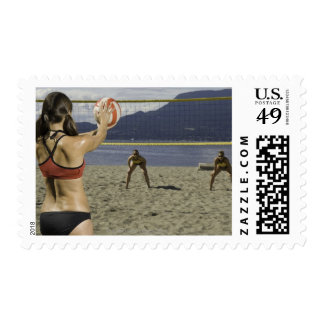 Women playing volleyball on beach postage