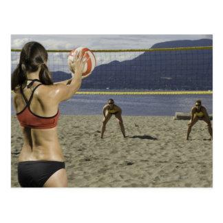 Women playing volleyball on beach postcard
