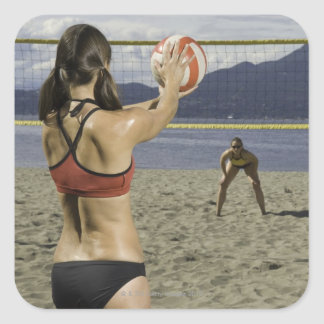 Women playing volleyball on beach square sticker