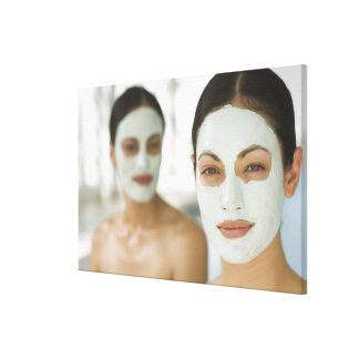 Women smiling in beauty mud masks canvas print