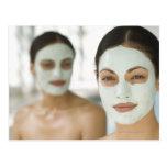 Women smiling in beauty mud masks postcard