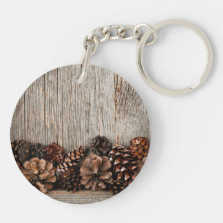Wood background with pine cones keychain
