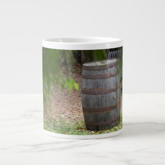 wooden barrel right with green frond left large coffee mug