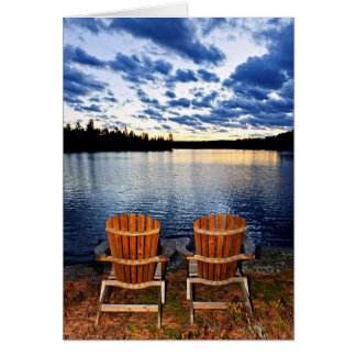 Wooden chairs at sunset on lake shore card