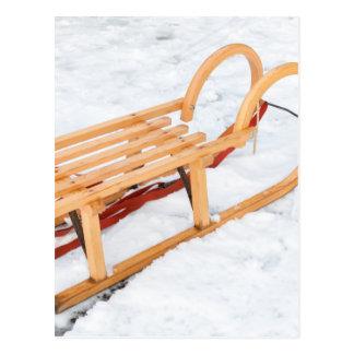 Wooden children sled in winter snow postcard