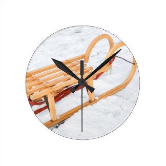 Wooden children sled in winter snow round clock