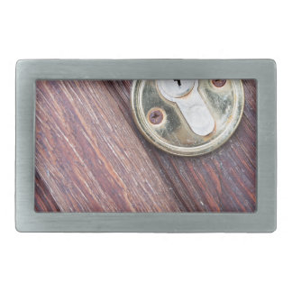Wooden door with a keyhole brass belt buckle
