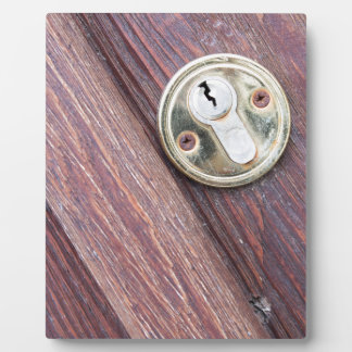 Wooden door with a keyhole brass plaque
