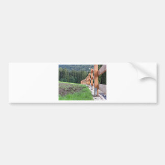 Wooden fence with forest in the background bumper sticker