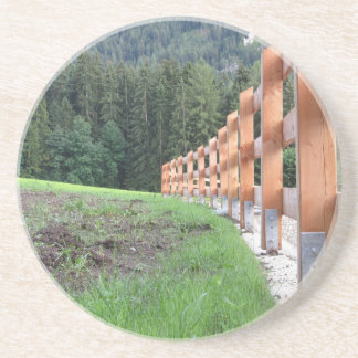 Wooden fence with forest in the background drink coaster