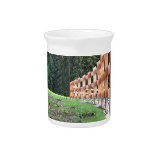 Wooden fence with forest in the background drink pitchers